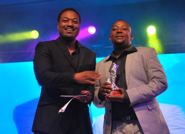Jimmy Kabwe presenting the award to Tip Top's manager Babu Tale