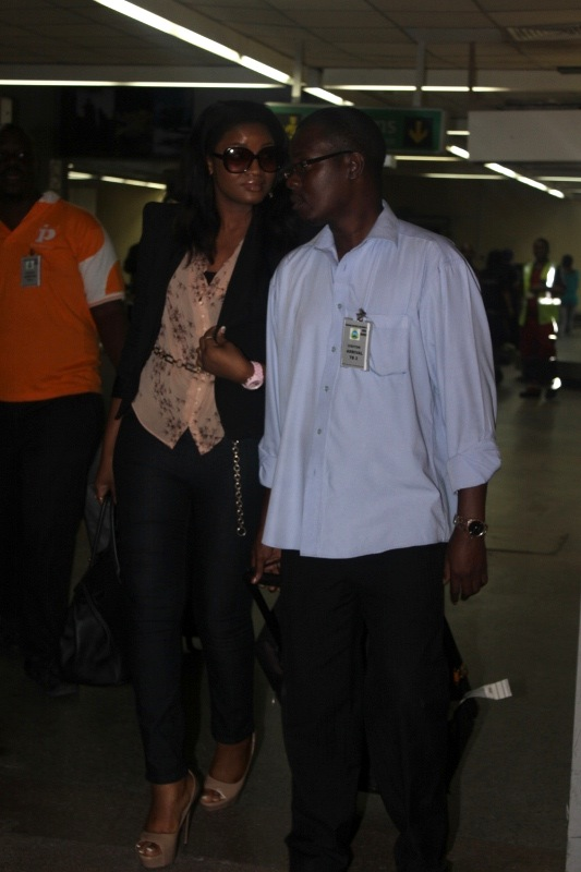 Peter Mwendapole escorting Omotola Jalade out of the airport