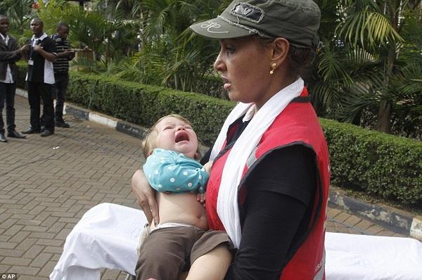 Mfanyakazi wa Red Cross akimbeba mtoto aliyekuwa ndani ya mall hiyo