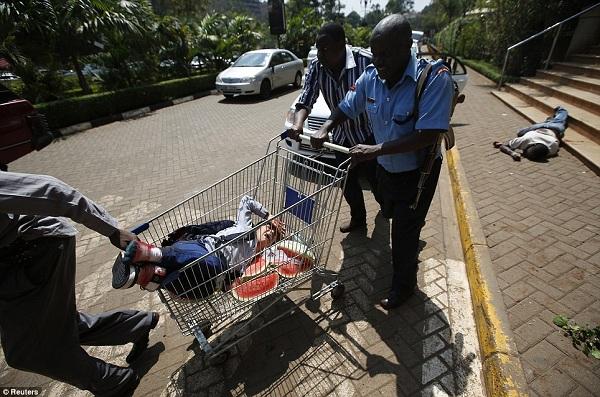Mwanamke aliyejeruhiwa akitolewa nje kwa kubebwa kwenye toroli la kufanyia shopping
