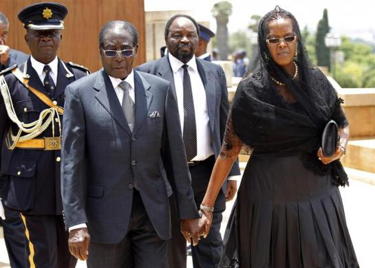 Zimbabwe's President Robert Mugabe and his wife Grace hold hands as they walk away after paying their respects at the coffin of former South African President Nelson Mandela, which is lying in state, at the Union Buildings in Pretoria